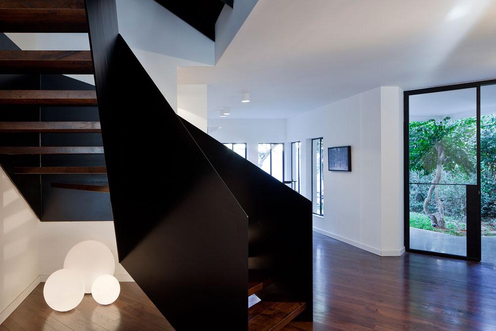 גרם המדרגות אל הקומות העליונות מוקם מול קיר המטבח, ותחתיו זורחים כדורים אקריליים בשלושה גדלים, של חברת '''bega''' (צילום: עמית גרון)
