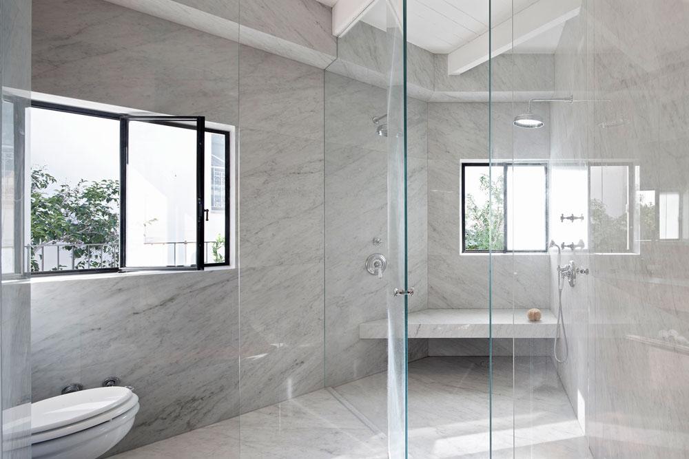 בחדר הרחצה מקלחון גדול ומשולש, בפינה של הקומה. הוא חופה בשיש קררה, שממנו גם הוכן ספסל נוח (צילום: עמית גרון)