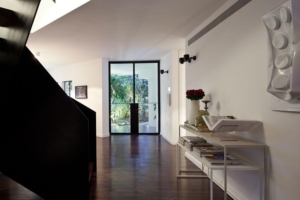 הכניסה. רצפת הפרקט עשויה עץ אלון מבוקע שנצבע בגוון שוקולד. כנגד הקיר הוצבו שתי קונסולות מברזל לבן, ונתלתה עליו עבודת פופ-ארט בצורת לבנת לגו גדולה ומעוכה, של האמן ame 72. קירות הבית לבנים, והחלונות הגדולים מוסגרו בברזל שחור (צילום: עמית גרון)
