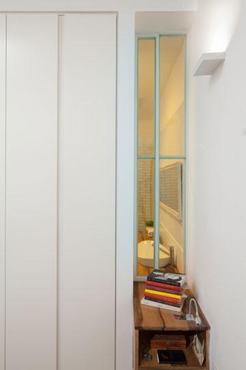 מחדר השינה אפשר לראות את אזור הכיור בחדר הרחצה. ארון הכיור נמשך דרך החלון והופך לשידת לילה בצדו השני (צילום: טל ניסים)