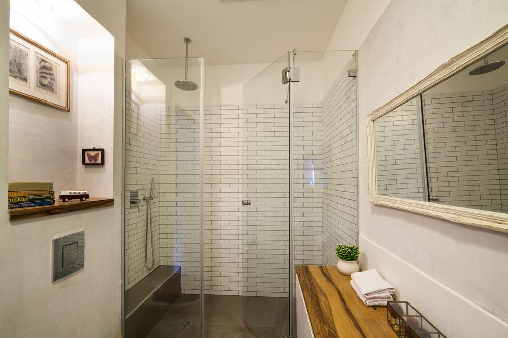 למרות גודלה המוגבל של הדירה נבנה בחדר הרחצה מקלחון מרווח ונוח. גם כאן שולבו מדפי עץ ועבודות אמנות (צילום: טל ניסים)