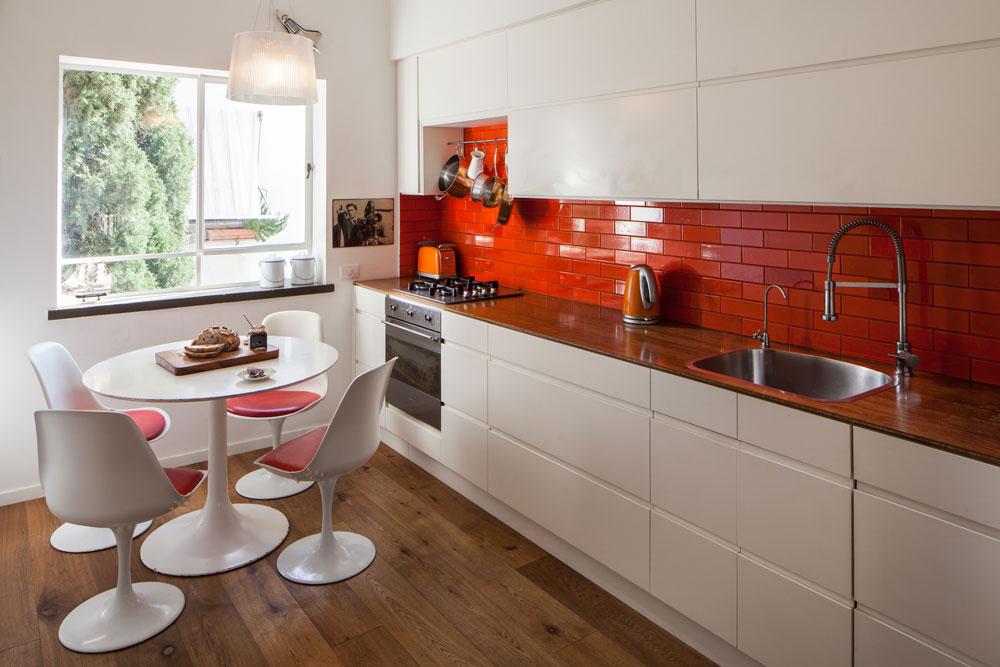 למטבח נבחרו אריחים בכתום-אדום בוהק, כדי לתת ''פאנץ''' למטבח, ומשום שהם מתאימים לפינת האוכל שהביא אתו הדייר: שולחן וכסאות בסגנון ''טוליפ'' של המעצב אירו סרינאן. הארונות לבנים כמו הקירות, ומשטח העבודה עשוי מעץ במבוק לבוד (צילום: טל ניסים)
