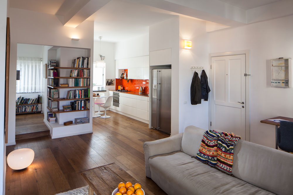 הרקע של הדירה נקי ובהיר. חום מוסיפים לחלל הפרקט, המדפים בנישות, הספרים ויצירות האמנות על הקירות (צילום: טל ניסים)