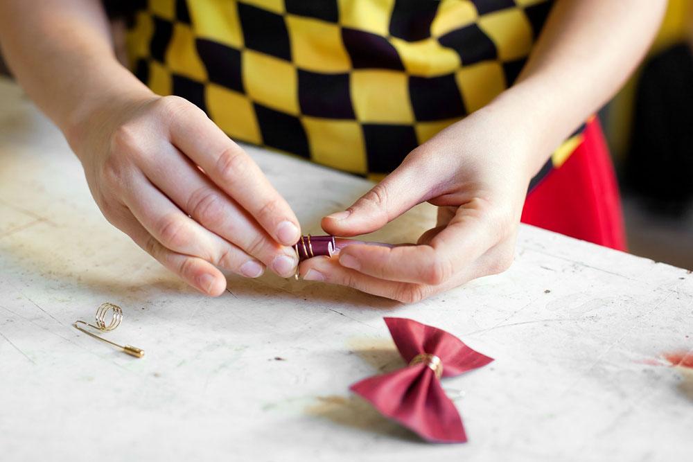 כרם קמינסקי עובדת על סיכות דש בצורת פפיונים (צילום: ענבל מרמרי)