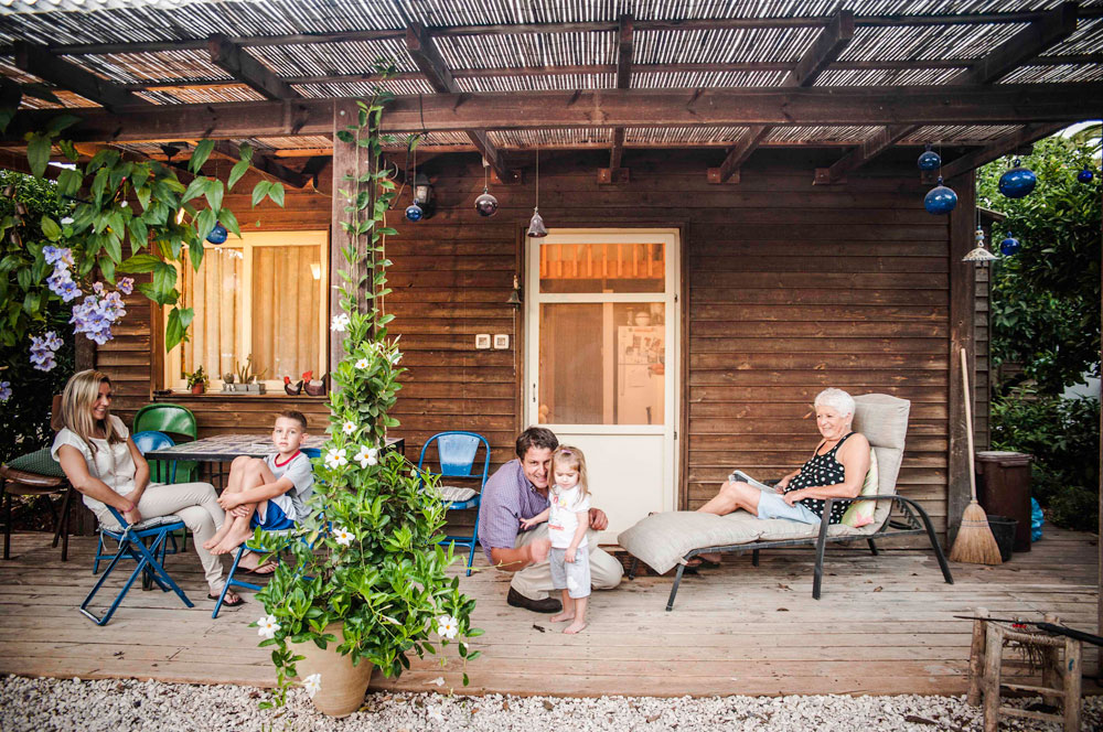 בני משפחת מאיק במרפסת הבית הקטן יותר, שאליו עברה אמו של גלעד (יושבת מימין). קרובים קרובים (צילום: גלעד רדט)