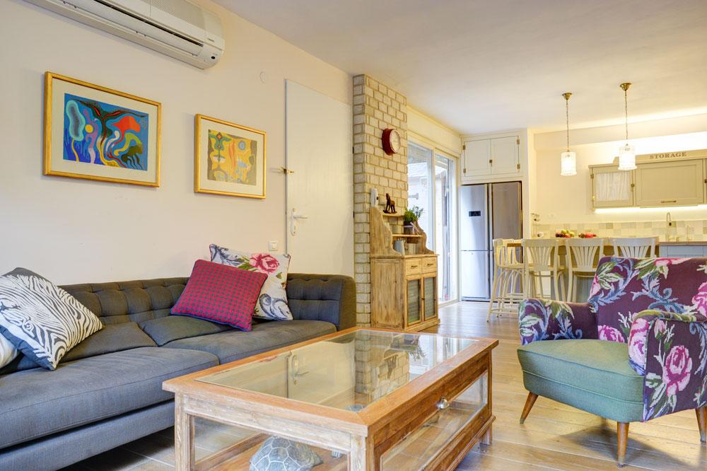 בסלון טקסטיל במגוון צבעים ודוגמאות ואילו המטבח (ברקע) מאופיין בצבעים בהירים ובעיצוב שקט יותר (צילום: אדריאן דודה)