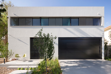 החזית שפונה לרחוב. מימין חניה ש''נבלעת'' בתוך הבית, משמאל דלת הכניסה הרחבה לחדר העבודה (צילום: שי אפשטיין)