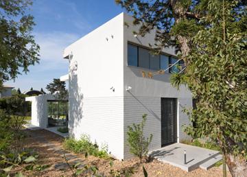 דלת הסטודיו מופרדת ממפלס הגינה באמצעות במה מבטון, וכך הוגדר מקום עבודה שאינו קשור לבית (צילום: שי אפשטיין)