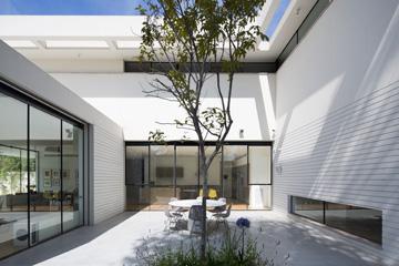 הפטיו צופה לסלון ולמטבח באמצעות חלונות גדולים. יש גם קיר משותף עם חדר העבודה, שבחלקו התחתון חלונות אופקיים (צילום: שי אפשטיין)