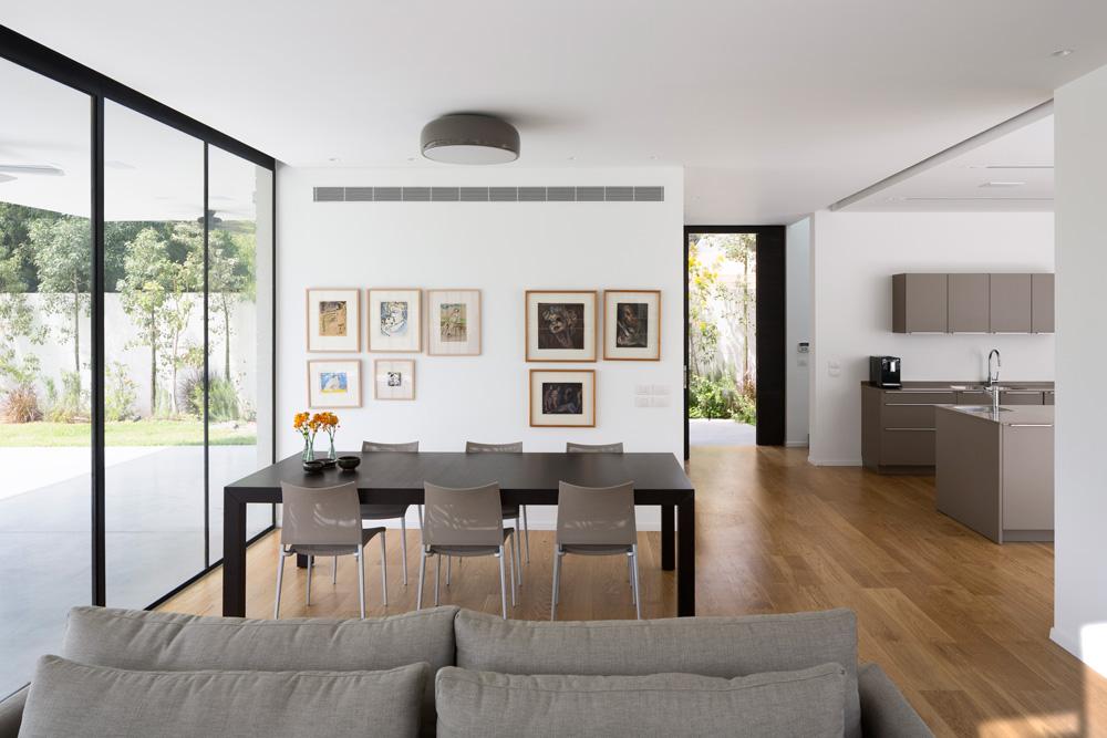מבט מהסלון לכיוון דלת הכניסה לבית. על הקיר נתלו יצירות אמנות שאספו בני הזוג עם השנים (צילום: שי אפשטיין)