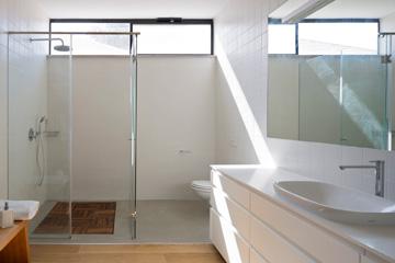 בחדר הרחצה של ההורים נמשך חיפוי הפרקט עד למקלחון והאסלה, שם הוא הופך לבטון מוחלק. חלון עליון מספק אור ואוויר (צילום: שי אפשטיין)