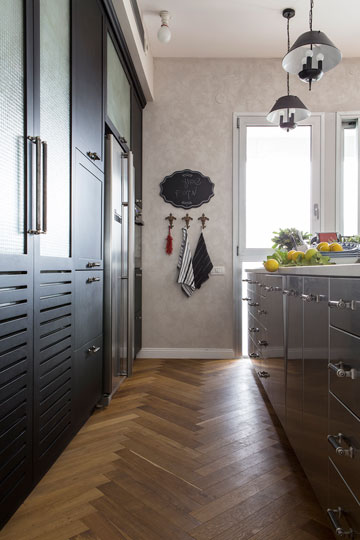 המטבח: ארונות מנירוסטה ומולם ארונות עץ שחורים, כשבתווך פרקט בדוגמת אדרת דג (צילום: איתי בנית)
