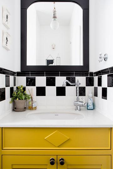 שירותי האורחים מעוצבים בשחור ולבן עם ארון צהוב עז לכיור - רמז לצבע המוניות בניו יורק (צילום: איתי בנית)