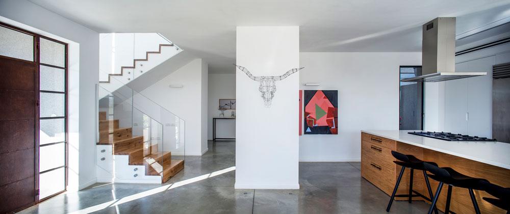 על העמוד תלוי פסל של קובי סיבוני, בן הקיבוץ, ועל הקיר ציורי אקריליק על בד של שירי לס. גרם המדרגות (משמאל) נבנה על ידי הנגר סבסטיאן קוך, שגם הוא פועל בקיבוץ (צילום: יואב גורין)