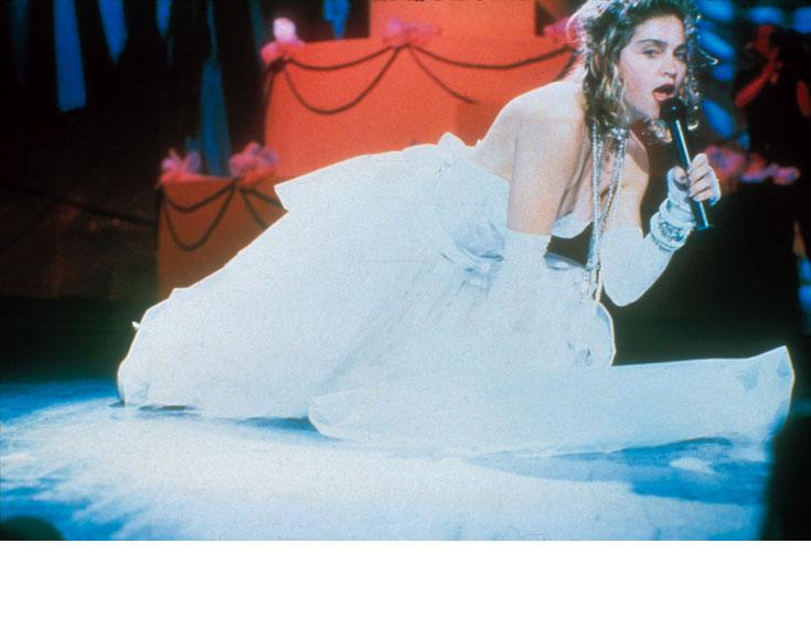 """עם התהילה הגיעו הפרובוקציות. סגנון הלבוש של מדונה מתחדד ומתבטא גם בהופעתה בסרט """"סוזאן סוזאן"""" משנת 1986, אך בתפנית בולטת: חושפני, פרובוקטיבי, מתריס. מדונה ממשיכה לאמץ מוטיבים מהניו-רומנטיק, ועל עטיפת האלבום היא מצולמת ככלה בשמלת טול לבנה, שחלקה העליון עשוי כמחוך רשת, מראה שמלווה אותה גם בסיבוב ההופעות (צילום: gettyimages)"""