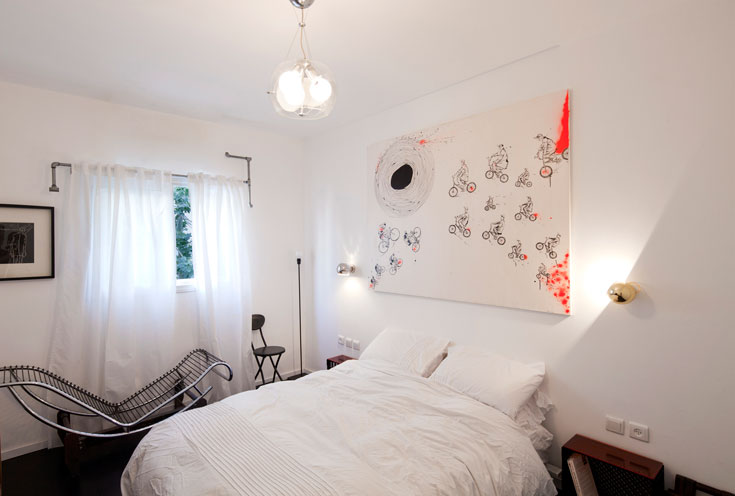 מוט הווילון עשוי מצינורות אינסטלציה, כדי להאריך את החלון. מעל המיטה תלוי ציור של גוטמן - מחווה לזוגות האופניים שנגנבו ממנה (צילום: אביעד בר נס)