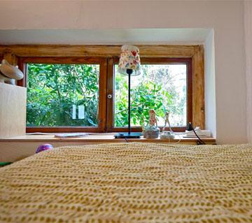 המיטה מיישרת קו עם העצים שנראים דרך החלון (צילום: איתי סיקולסקי)