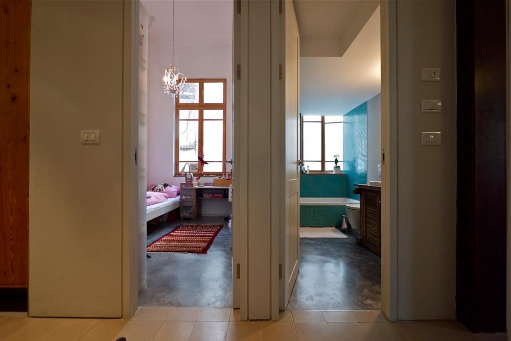 משמאל: חדרה של בת התשע. הוא אמנם קטנטן, אך לא מחניק בזכות התקרה הגבוהה. בחדר עירוב של ישן וחדש: הגובה והחלונות שייכים לעבר, לבתים שנבנו כאן פעם, והרצפה מחופה בטון מוחלק, כמו ביתר החדרים. שולחן הכתיבה משוק הפשפשים, הכיסא שלצדו מאיקאה. מימין: חדר הרחצה, שבו התקרה מונמכת. במקום הבוידם הישן ''יושב'' עליו חדר ארונות קטן המשמש את הבת הבכורה (צילום: איתי סיקולסקי)