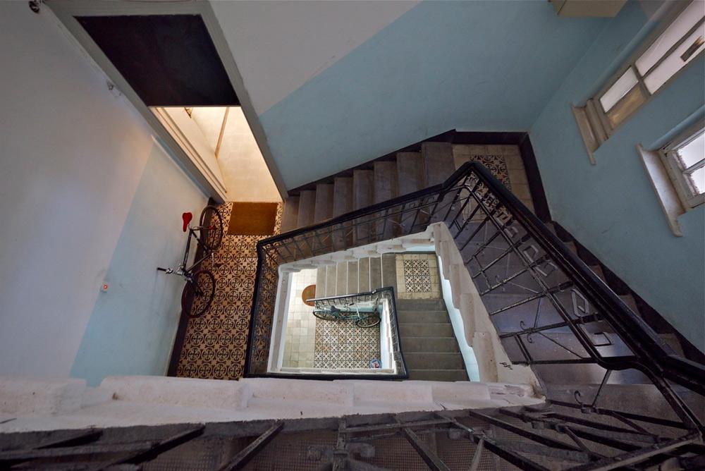 בבניין חדר מדרגות יפהפה בסגנון הישן. החללים בגובה שמזמן לא מקובל בבנייה בישראל - 3.82 מטרים - ואלבז השתמש בו כדי לנצל כל מטר בדירה כך שתתאים למשפחה עם 3 ילדים (צילום: איתי סיקולסקי)