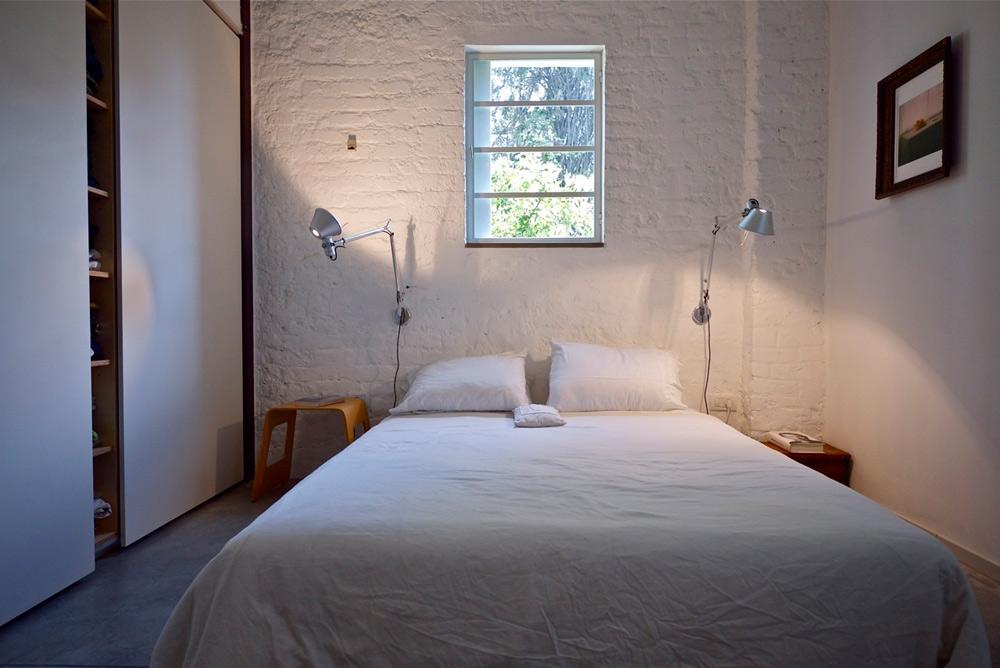 חדר ההורים בהיר ומינימליסטי.  המיטה בחדר ההורים נשענת על קיר לבני סילקט, שנחשפו בשיפוץ ונצבעו לבן. משני צידיה עירוב של סגנונות ומחירים: מצד אחד שרפרף פשוט של איקאה, מצד שני שידה קטנה מהמזרח, ולקיר צמודות שתי מנורות מבית המותג היוקרתי ''ארטמידה'' (צילום: איתי סיקולסקי)