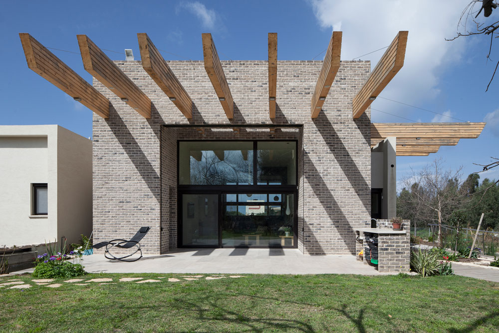 קורות עץ אשוח בולטות מהמבנה, והחלונות הגדולים שוקעו לעומק הבית, כדי למתן את קרני השמש (צילום: אביעד בר נס)