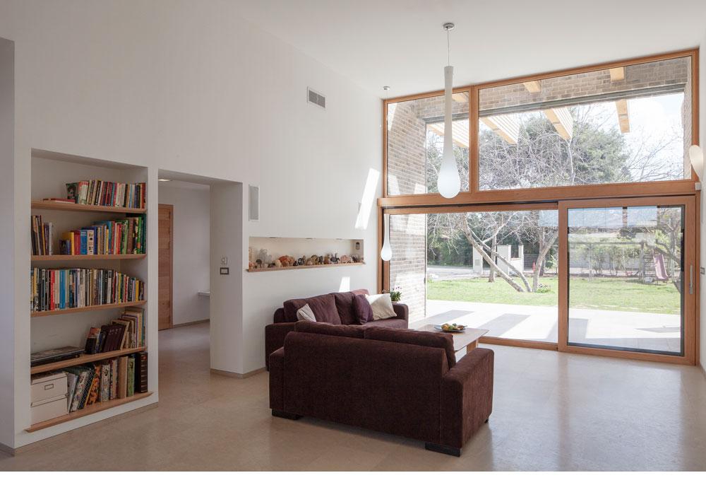 כאן אפשר לראות היטב את היתרון שבחלון השקוע. רהיטים רבים מלווים את המשפחה שנים. ספות חדשות נקנו לסלון, ומעליהן נישה שמוקדשת לאוסף הכבשים של בעלת הבית (צילום: אביעד בר נס)