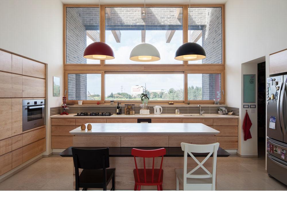 הרצפה חופתה שיש דארמה, המטבח עשוי עץ מייפל. נגיעות של שחור, לבן ואדום מוסיפים גופי התאורה והכסאות (צילום: אביעד בר נס)
