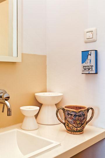 """כד מסורתי לנטילת ידיים וקופה של קק""""ל בשירותים. """"אין פינה שלא חשבתי עליה"""", אומרת לוי-מיצוניק (צילום: אבישי פינקלשטיין)"""