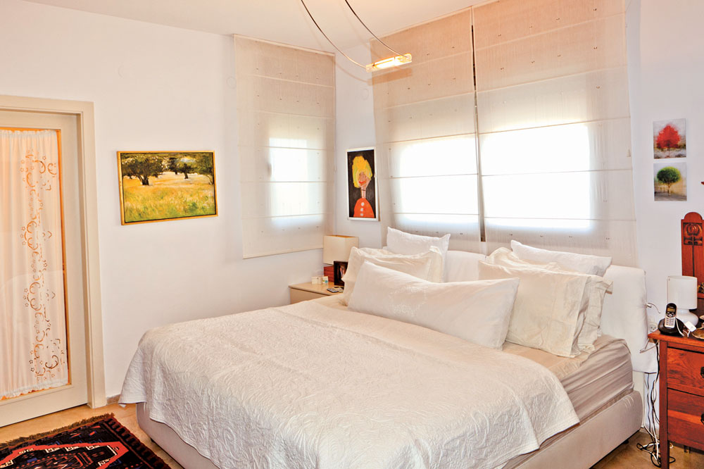 מיטה ענקית תופסת את רוב חלל החדר. מעליה תלוי ציור של אישה שציירה הבת, עלמה, כשהייתה בת חמש (צילום: אבישי פינקלשטיין)