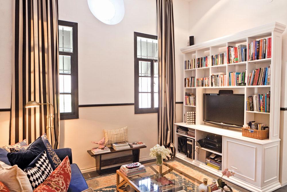 הספרייה נבנתה לפי מידות הקיר ומסביב למסך הטלוויזיה: ספסל ישן הוצמד לקיר בין שני החלונות ומשמש כסטנד למגזינים של עיצוב. מבט נוסף לסלון (צילום: אבישי פינקלשטיין)