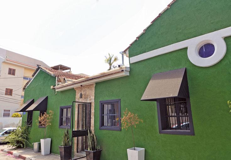 חזית הבית טויחה בצבע ירוק דשא עמוק, גוון לא סטנדרטי שמשתלב בקלות בשכונת נווה צדק הייחודית (צילום: אבישי פינקלשטיין)