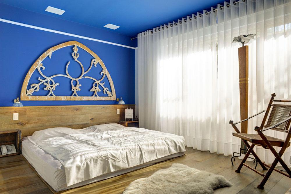 התקרה וקיר אחד של חדר השינה נצבעו בכחול. פרקט העץ ''עוטף'' את במת המיטה ומטפס גם על הקיר שמאחוריה. מעל ראש המיטה נתלה חלק מדלת מקושתת ישנה ושני אגזי תפוזים ישנים הוסבו לשידות לילה (צילום: Hadrien Daudet)