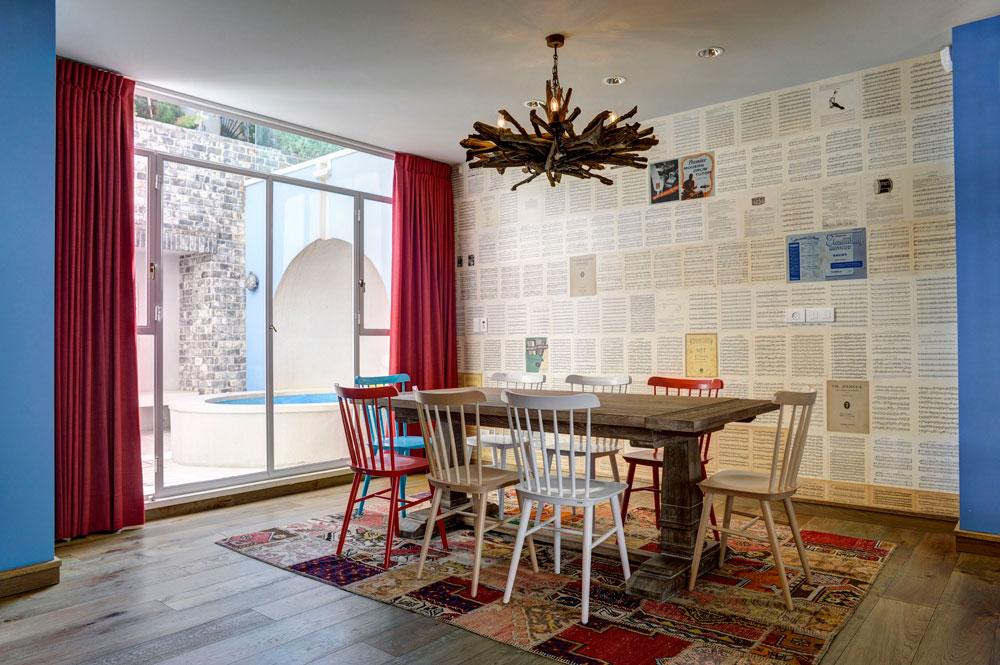 פינת האוכל פונה לחצר שבה ג'קוזי בנוי, המשותפת גם לחדר השינה. על הקיר הודבקו דפים שפורקו מחוברות תווים ישנות. שטיח טלאים, שולחן אבירים וכסאות צבעונייים משלימים את החלל (צילום: Hadrien Daudet)