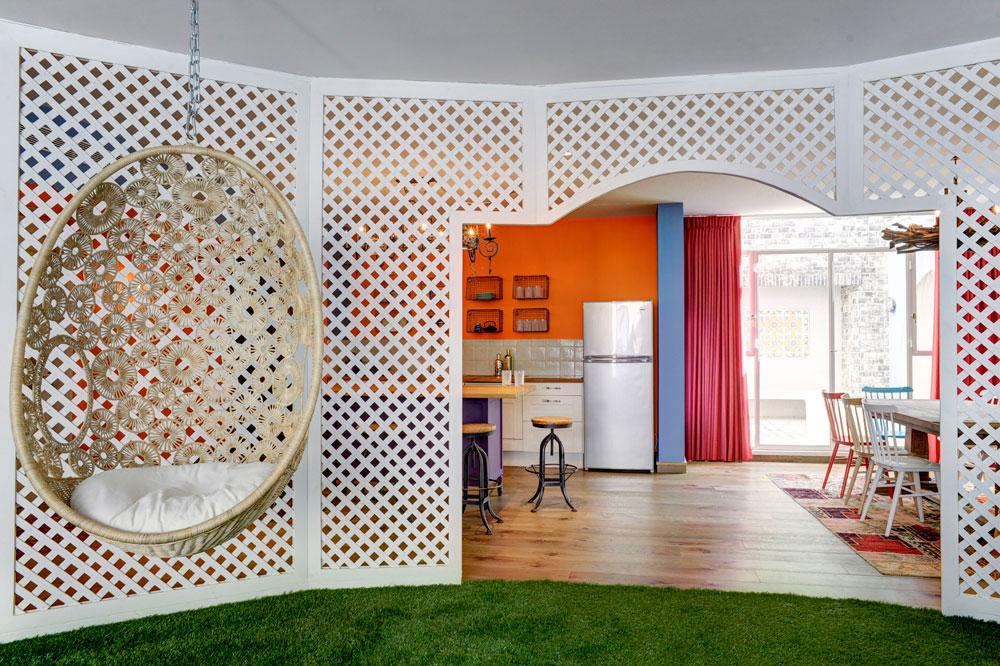 שער דרמטי נפער בשבכה, ומעברו השני רצפת פרקט וצבעים עזים שמגדירים את המטבח ואת פינת האוכל (צילום: Hadrien Daudet)