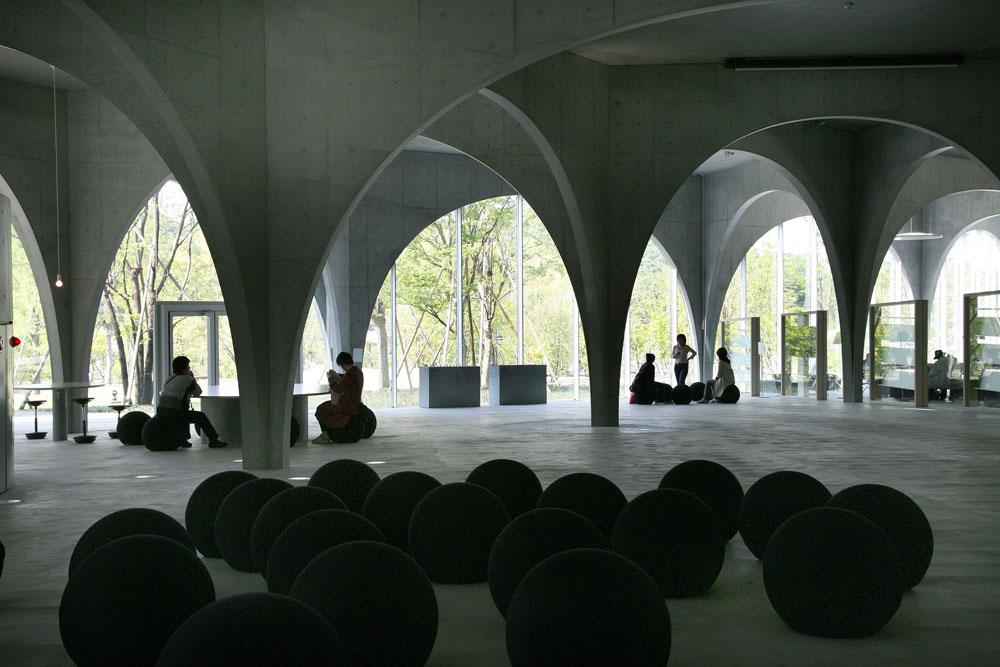 ספריית אוניברסיטת טאמה לאמנות מורכבת ממערכת קשתות בטון חשוף. הבניין, שנראה כאוהל ענק הפתוח אל הנוף, משמש לא רק כספרייה אלא כמקום מפגש לסטודנטים (צילום: Tomio Ohashi)