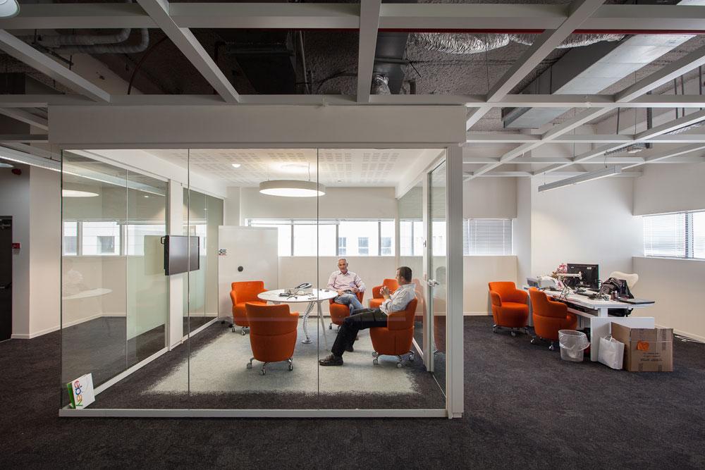 שקוף ונגיש. עמדת העבודה של המנכ''ל, ובסמוך לה חדר הישיבות השקוף של ההנהלה (צילום: טל ניסים)