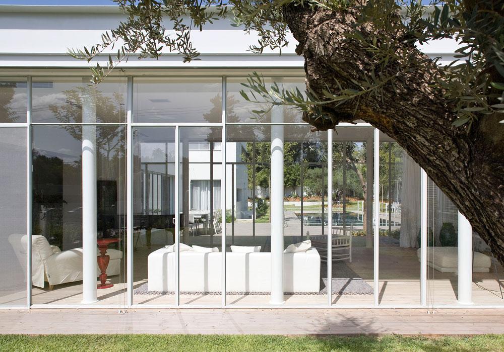 את הסלון השקוף מכנה האדריכל ''פטיו מקורה'' (וילונות הסטה מספקים פרטיות כשצריך), ואילו הדיירים מכנים אותו ''הסוכה'', משום שהם מרגישים בו בחוץ ובפנים גם יחד (צילום: עמית גרון)