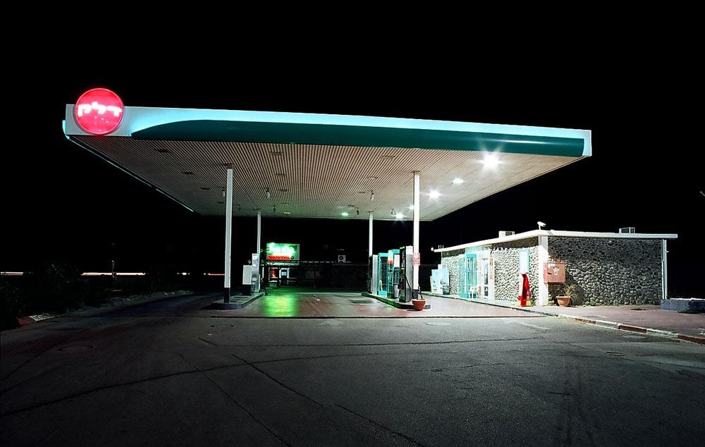 תחנת דלק בקיבוץ גינוסר, על שפת הכנרת. במרכז הסככה נמצאות המכונות הגדולות, שמזכירות מכונות-מזל בבתי הימורים (וממכרות בהתאם) (צילום: שי שאול)