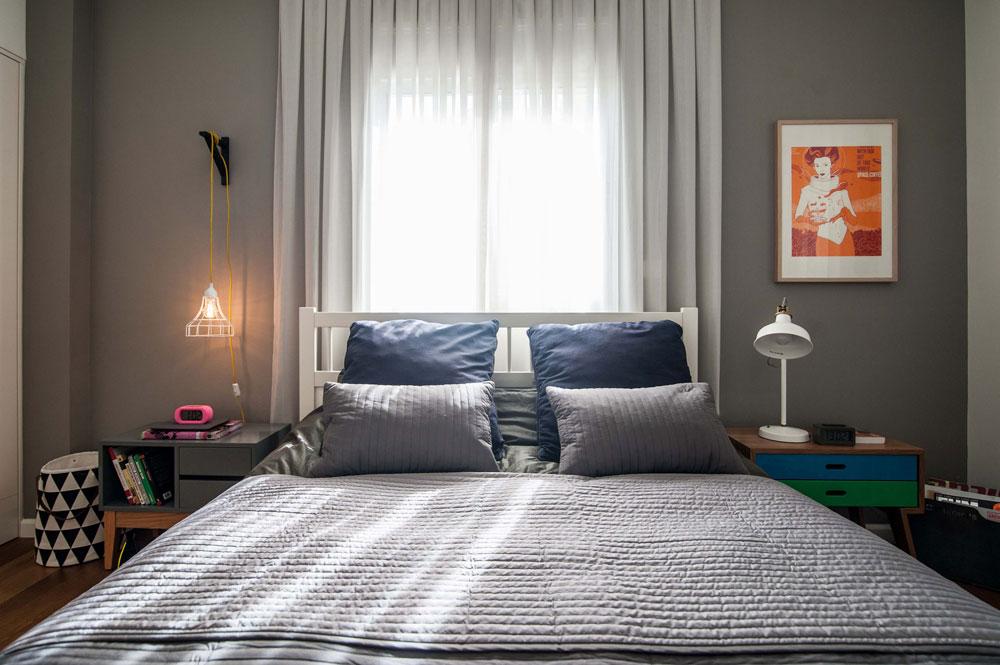 חדר ההורים: וילון ארוך ובהיר במרכז קיר אפור משמש גם כגב למיטה הזוגית, שמשני צידיה שידות לילה ומנורות לא תואמות  (צילום: גלעד רדט)