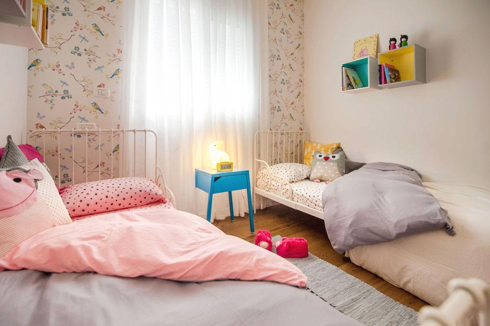 """בחדר השינה של הילדות חופה הקיר שמול הדלת בטפט עם דוגמה עדינה של ציפורים. זו מול זו הוצבו שתי מיטות ברזל (""""איקאה""""), שמעל כל אחת מהן נתלו שתי קוביות אחסון בגוונים שונים (צילום: גלעד רדט)"""