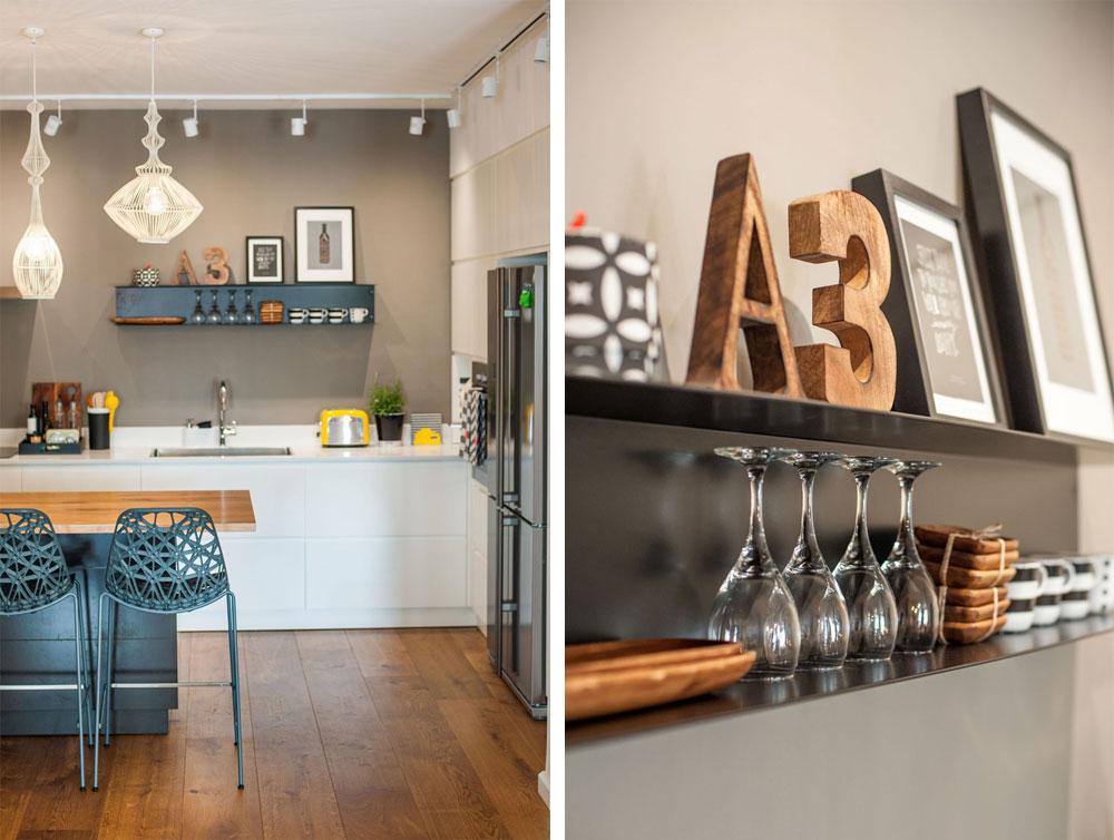 המטבח תוכנן בצורת האות ר': ארונות גבוהים בצד ומול החלל הפתוח ארונות נמוכים בלבד. על הקיר האפור בולט מדף פח שהוזמן במיוחד, נצבע בשחור וקושט בכלים שנבחרו בקפידה ובשני הדפסים בשחור-לבן. סביב ה''אי'' שלושה כסאות בר אפורים בדוגמה מחוררת ומעל שלוש מנורות ברזל לבנות, בשלוש צורות שונות של ''כלובים'' (צילום: גלעד רדט)