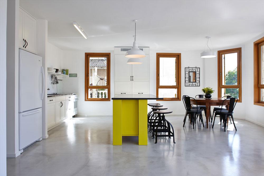 רצפת האבן כוסתה בבטון מוחלק דק במיוחד, והקיר שהפריד בין המטבח לפינת האוכל הוחלף ב''אי'' שנצבע בצהוב עז (צילום: עדי גלעד)