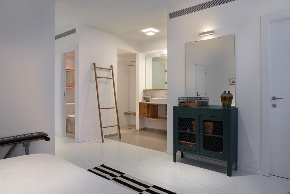 מבט מאזור המיטה לחדר הרחצה הפתוח, שבמרכזו ארון כיור שנבנה בתוך נישה, מימין אמבטיה ומשמאל מקלחון עם ספסל בטון (צילום: עדי גלעד)