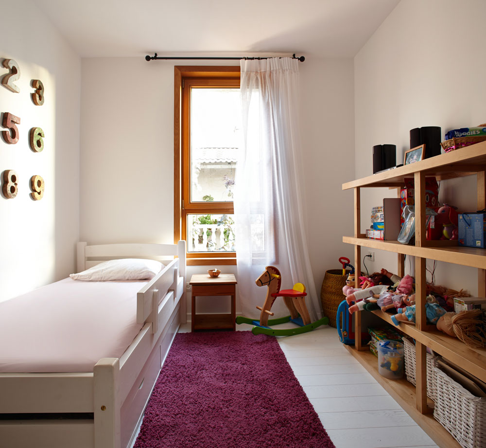 בחדר הילדה רהיטי עץ, שמתאימים למסגרת החלון. על הקיר מעל המיטה נתלו ספרות עץ (צילום: עדי גלעד)