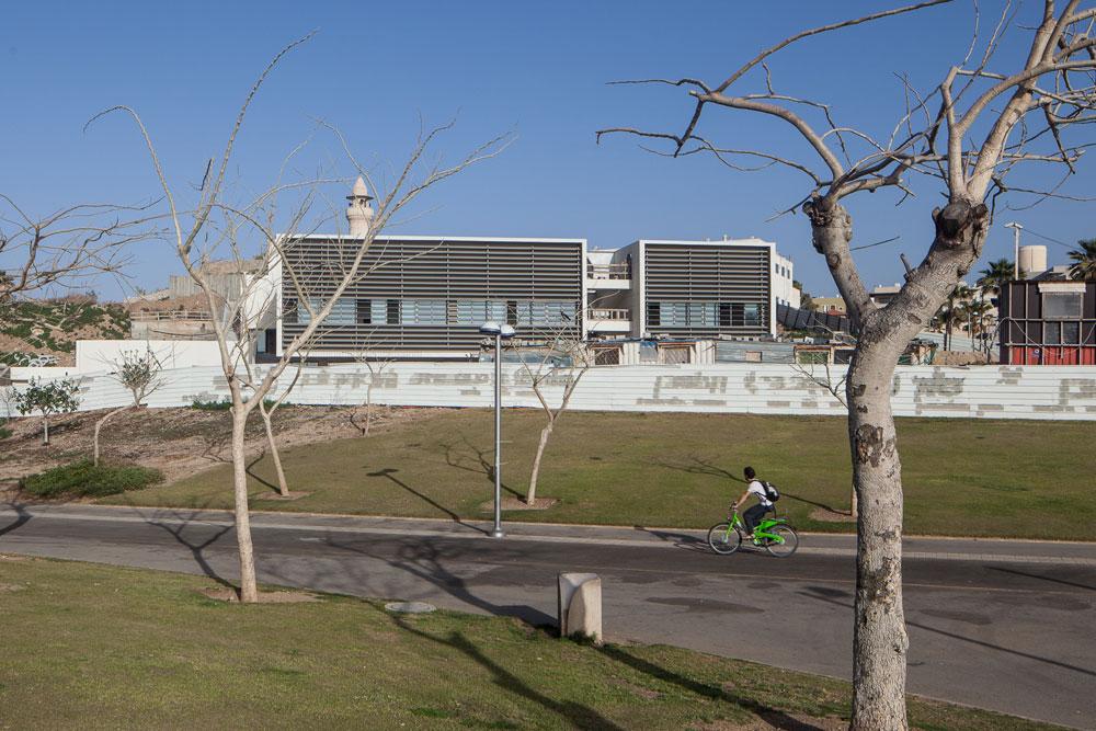 """אולם הספורט של בי""""ס חסן ערפה ביפו. המסה הגדולה של הבניין מיטשטשת בנוף, מכיוון שמרביתה קבורה באדמה. הבדלי הגובה גם איפשרו שתי כניסות נפרדות - לתלמידים ולקהל הרחב (צילום: טל ניסים)"""