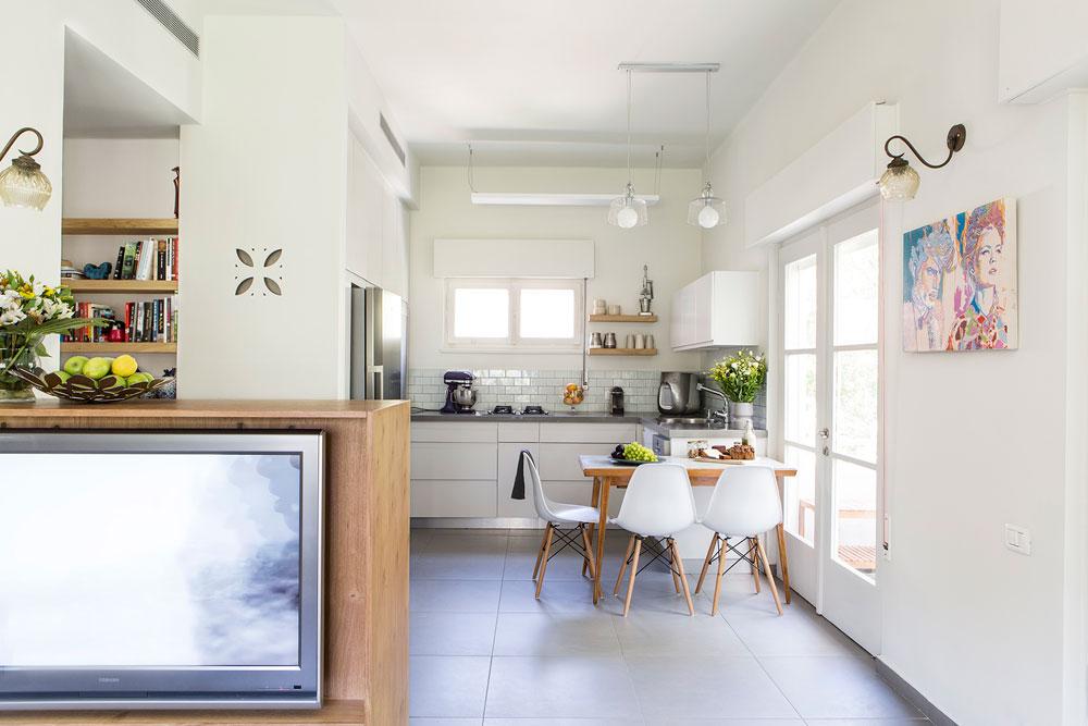 מבט מהסלון לכיוון המטבח, שנבנה בצורת האות ח'. פינת האוכל סמוכה לאחת היציאות למרפסת, ומורכבת משולחן עץ נפתח ישן וכסאות לבנים חדשים בסגנון אימס (צילום: איתי בנית)