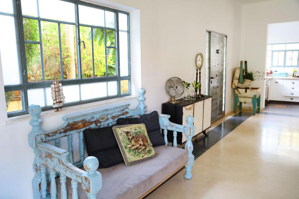 הספה תכולה נבנתה ממיטה זוגית ישנה, שדנציג חתכה וצבעה בתכלת. דלת הכניסה, שעשויה פח, שויפה ונצבעה בלכה (צילום: ליאור דנציג)