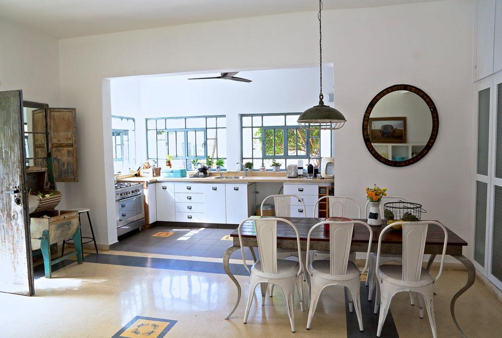 המטבח של ליאור דנציג. משמאל: מכונת כביסה עתיקה מעץ, שמשמשת עכשיו לאחסון פירות וירקות. דלתות הארונות נצבעו לבן והידיות הוחלפו (צילום: ליאור דנציג)