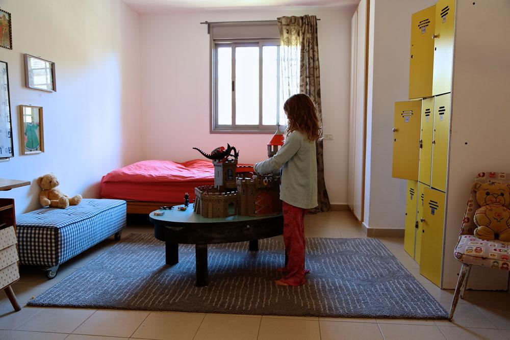 שני הילדים חולקים חדר גדול. מיטה וחצי נבנתה ממשטחי הובלה שחוברו יחד לפלטה. במרכז החדר שולחן אוכל אובלי מבית ההורים, שרגליו קוצרו. ארון לוקרים הפך לארון בגדים (צילום: ליאור דנציג)