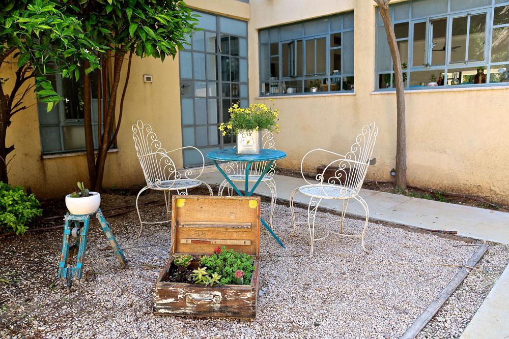 רחבת הכניסה לסטודיו של דנציג, שנבנה במקום החניה, בצמוד למטבח. מזוודות ישנות נצבעו והוסבו לערוגות קטנות (צילום: ליאור דנציג)